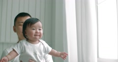 Young asian father lovingly holding up cute baby while they play together,slow Stock Footage