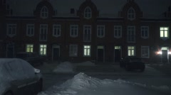 Snowfall in townhouse residential area at night Stock Footage