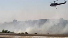Helicopter dumping water on fire near a canal Stock Footage