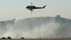 A helicopter drops a load of water into the smoke of a fire Stock Footage