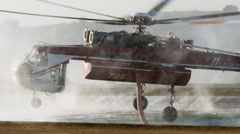 Rising water vapor surrounds a firefighter helicopter as it takes off after Stock Footage