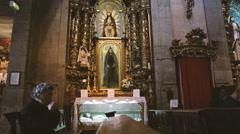 Old woman praying inside the Capela de Santa Catarina - stock footage