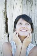 Woman leaning against tree trunk, looking up and smiling hopefully Stock Photos