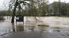 Floodwaters ripple around a noticeboard at an inundated riverside park Stock Footage