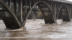 Close view of floodwater swirling around the supports of a concrete bridge in - stock footage