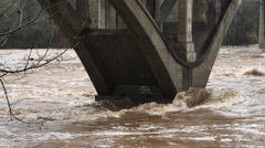 Close-up floodwater rising on a concrete bridge support in the rain - stock footage