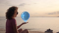Woman holding Earth Hologram in hand near sea.  glowing and shining futuristic Stock Footage
