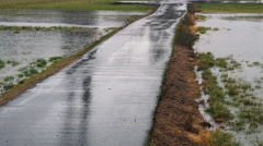 A concrete driveway in the rain with flooded fields on either side Stock Footage