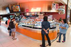 air passengers choose fast food to buy, Bangkok airport - stock photo