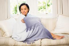 Stock Photo of Attractive brunette on the sofa under blanket