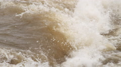 Close-up churning rapids on a muddy river in flood Stock Footage