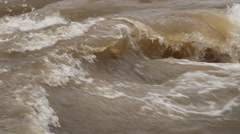 Close-up churning rapids on a river in flood - stock footage