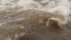 Close-up churning rapids on a muddy river in flood - stock footage