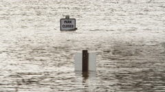 A Park Closed sign standing in moving floodwater - stock footage