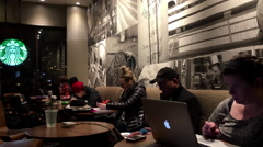 One side of people enjoying coffee at Starbucks Stock Footage