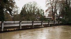 Flooding stream almost touching the bottom of a bridge in a suburban Stock Footage