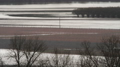 Wide view of flooded low-lying farmland in rain Stock Footage