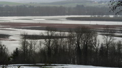 View from a snowy hilltop of flooded low-lying farmland in rain Stock Footage