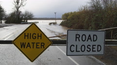 High Water and Road Closed signs on a barricade in front of a flooded road and - stock footage