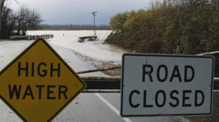 High Water and Road Closed signs on a barricade blocking a flooded road and - stock footage