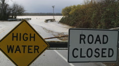 High WAter and Road Closed signs blocking a flooded road and bridge Stock Footage