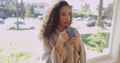 An attractive young brunette woman drinking from a mug Stock Footage