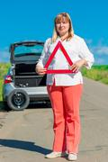 Portrait of a woman of mature age with warning triangle - stock photo
