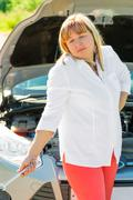 confused woman and a broken car in a journey - stock photo