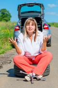 Annoyed woman sitting on the bursting of the wheel and waiting for help Stock Photos