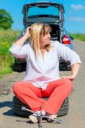mature female driver sitting in the spare wheel on a sunny day - stock photo