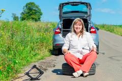 Happy female driver at the wheel sitting near a broken car - stock photo
