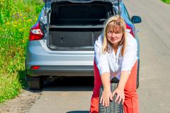 the female spare wheel rolls on the road - stock photo