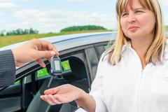 The seller presents the woman key from the new car Stock Photos