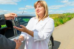 female 50 years, bought a new car and get key - stock photo