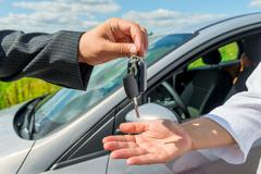 The solemn transfer the key the buyer of a new car - stock photo