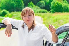 mature driver near her beloved car - stock photo