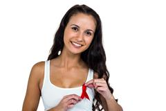 Portrait of smiling woman adjusting red ribbon Stock Photos