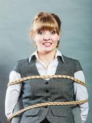 Kidnapped woman tied with rope to chair. - stock photo
