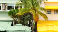 Miami Beach Ocean Drive scene with awnings of color and palm trees Stock Footage