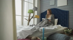 Blonde reading a book while sitting in bed. Stock Footage