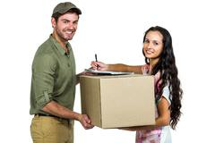 Stock Photo of Woman signing for pack delivery with smiling postman