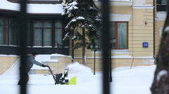 Man removes snow by using the snowplow with tracks around the house. Stock Footage