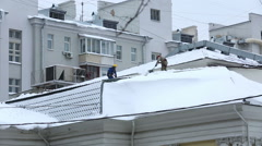 Stock Video Footage of Industrial climbers removed the snow from the roofs of houses.