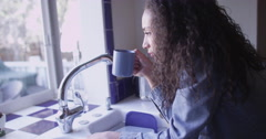 Young beautiful mixed ethnic woman having a morning drink Stock Footage
