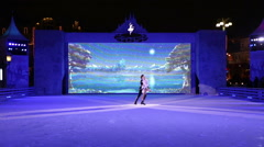 Young pair skaters dancing on the ice rink in the spotlight. - stock footage