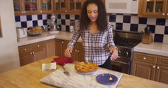 Attractive young mixed ethnic woman cutting apple pie Stock Footage