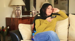Muslim woman watching tv Stock Footage