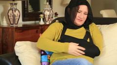 Muslim woman with a broken arm wearing arm brace 2 Stock Footage