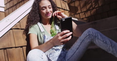 Beautiful young mixed ethnic woman looking at cellphone on stairs - stock footage