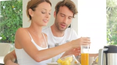 Cheerful couple having breakfast together - stock footage